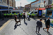 People walk by heavy police forces who are deployed in Dover city centre on Saturday, Sept 5, 2020 - ahead of warnings announced for a rival far-right and pro-migrant groups preparing to descend on the coastal town on Saturday, Sept 5, 2020. fears of violence against the refugees announced by far-right groups who are expected to assemble to demonstrate over migrant crossings. Pro-migrant protesters are already gathered in the town on Saturday amid a heavy police presence. Dover MP Natalie Elphicke has urged people to stay away from the protests given the backdrop of the Covid-19 pandemic. British media reports say that on Friday, an activist group projected pro-immigrant messages onto the White Cliffs of Dover ahead of the protests saying 'Rise above fear. Refugees welcome' (VXP Photo/ Vudi Xhymshiti)