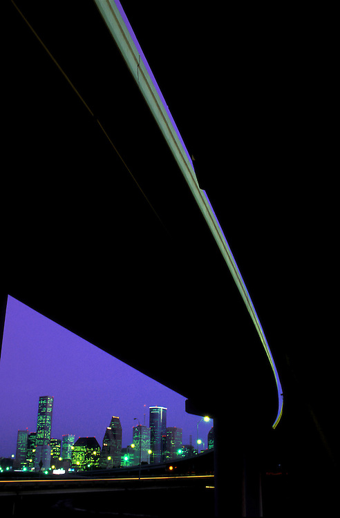 View from under a freeway overpass of the downtown Houston, Texas skyline at night.
