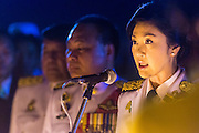 05 DECEMBER 2013 - BANGKOK, THAILAND: YINGLUCK SHINAWATRA (center) the Prime Minister of Thailand, reads a proclamation honoring the King at the celebration of the birthday of the King in Bangkok. Thais observed the 86th birthday of Bhumibol Adulyadej, the King of Thailand, their revered King on Thursday. They held candlelight services throughout the country. The political protests that have gripped Bangkok were on hold for the day, although protestors did hold their own observances of the holiday. Thousands of people attended the government celebration of the day on Sanam Luang, the large public space next to the Grand Palace in Bangkok.     PHOTO BY JACK KURTZ