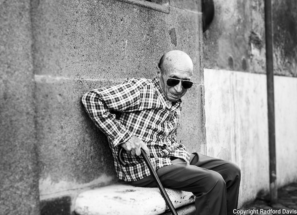 An elderly man sits outside his home in Rome.