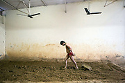 An Indian Khusti wrestler flattens the mud arena before a training session at a wrestling Akhara in New Delhi, India. Pehlwani, or kusti is a form of wrestling from South Asia. It was developed in the Mughal Empire by combining native malla-yuddha with influences from Persian koshti pahlavani. A practitioner of this sport is referred to as a pehlwan.