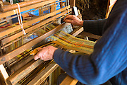 Craftsman using traditional loom to weave wool for handmade woolen scarf at Croft Wools and Weavers, Applecross in the Highlands of Scotland