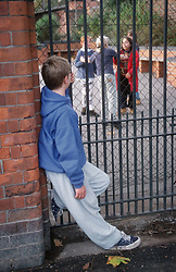 Young boy excluded from school looking through metal railings at children playing in playground,