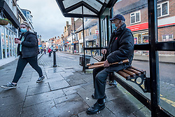 © Licensed to London News Pictures. 15/12/2020. RICKMANSWORTH, UK. A man wearing a facemask sits at a bus stop in Rickmansworth, Hertfordshire.  The historic town will be elevated to Tier 3 Covid Alert Level tomorrow, as part of the Three Rivers District Council area joining London and other areas of the South East as the number of coronavirus cases continues to rise.  Photo credit: Stephen Chung/LNP