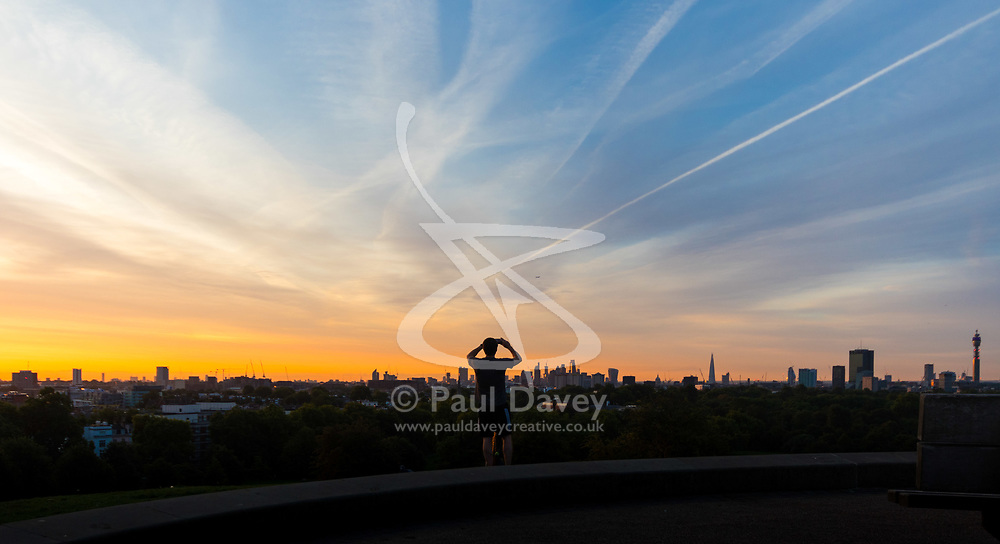 London, August 16 2017 . A man takes a photograph of the city skyline from the top of Primrose hill as London wakes up to a glorious sunrise. © Paul Davey.
