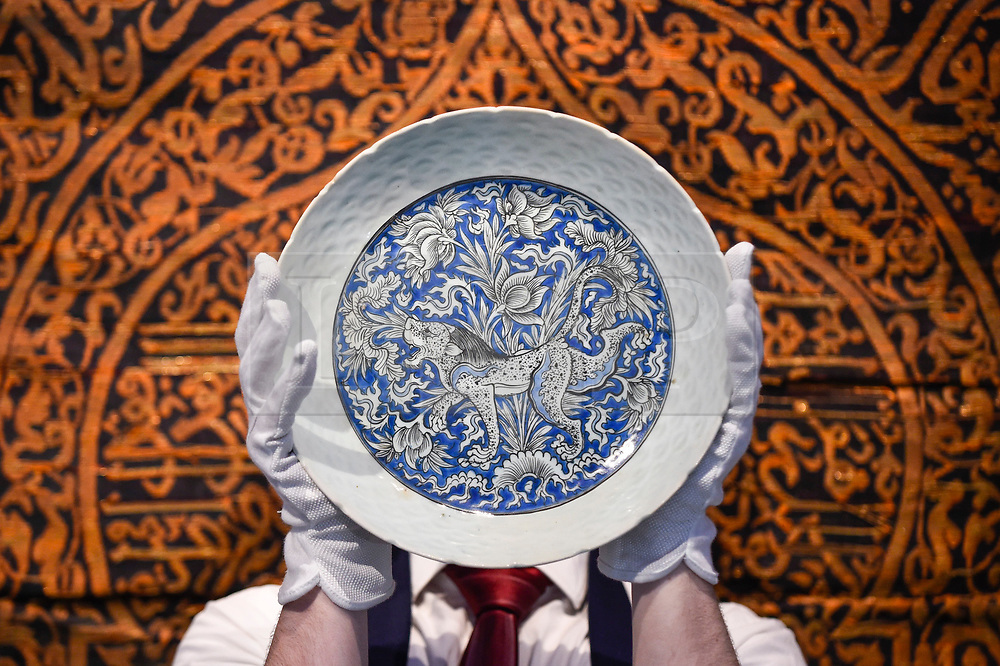"""© Licensed to London News Pictures. 18/10/2019. LONDON, UK. A technician presents a """"Safavid blue and white pottery dish depicting a lion"""", Persia, 17th century (Est. GBP8,000-12,000).  Preview of Islamic, Indian and Middle Eastern art to be auctioned at Sotheby's, New Bond Street, on 22 and 23 October.  Photo credit: Stephen Chung/LNP"""
