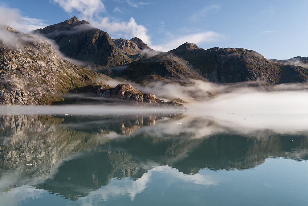 Morning fog, which had obscured all of the mountains, lifts from the water of Glacier Bay, Alaska