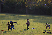 On the second day of the Easter Bank Holiday during the  lockdown, a restriction imposed by the UK government during the Coronavirus pandemic, young men play football together in the early evening in Ruskin Park, a public green space in Lambeth, south London, on 11th April 2020, in London, England.