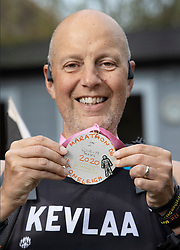 © Licensed to London News Pictures. 11/04/2020. Stoneleigh, UK. Kevin Webber holds up a home made medal after crossing the finishing line on the equivalent last Stage of the Marathon des Sables ultramarathon in his Surrey garden during lockdown. Kevin has run the entire 230Km (143 miles) 6 stage race in his small back and front gardens, completing 2734 laps, over 6 days - finishing today. Kevin, who was diagnosed with terminal prostate cancer just over 5 years ago was due to take part in his 5th consecutive running of what is described as the 'toughest foot race on Earth' through the Sahara Desert in Southern Morocco this month, but the 2020 six day race has been postponed until September.  Kevin is raising funds for the National Emergencies Trust Coronavirus Appeal who will distribute the funds to where they are needed most in the UK and he will jointly split what he raises with Prostate Cancer UK. Photo credit: Peter Macdiarmid/LNP