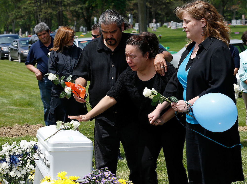"""""""Rest in His Arms"""" founder Susan Walker (R) helps the grandparents of an abandoned newborn boy visit his casket during a burial service at All Saints Cemetery in Des Plaines, Illinois, United States, June 19, 2015. More than a year after he was found dead in a plastic shopping bag on a Chicago sidewalk, the baby boy was buried by a non-profit group """"Rest in His Arms"""" after abandoned by his teenage mother, who is charged with murder.   REUTERS/Jim Young"""