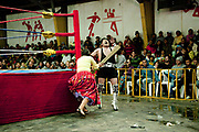 Alicia Flores female wrestler hitting male opponent with a wooden plank, out of ring with crowd in background. Lucha Libre wrestling origniated in Mexico, but is popular in other latin Amercian countries, including in La Paz / El Alto, Bolivia. Male and female fighters participate in the theatrical staged fights to an adoring crowd of locals and foreigners alike.
