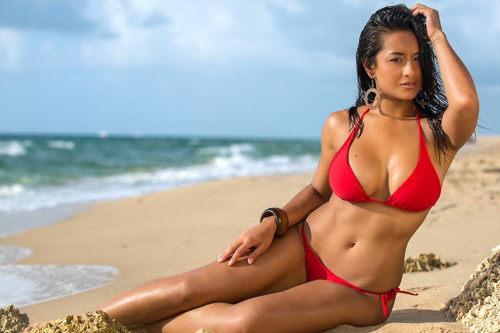 Portrait of hot female in red bikini sunbathing over the blurred beach background