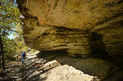 A hiker walks past one of the many geologic features along the Yellow Rock Trail in Devil's Den State Park.<br /> <br /> Devil's Den State Park is an Arkansas state park located in the Lee Creek Valley of the Boston Mountains in the Ozarks. Devil's Den State Park contains one of the largest sandstone crevice areas in the U.S. The park contains many geologic features such like crevices, caves, rock shelters, and bluffs. The park is also known for its well-preserved Civilian Conservation Corps (CCC) structures built in the 1930s. These structures, still in use today include cabins, trails, a dam, and shelter.<br /> <br /> Devil's Den State Park has approximately 64 miles of trails that are popular with hikers, mountain bikers and horseback riders. One popular trail is the Devil's Den Self-Guided Trail (1.5 miles long) that passes by Devil's Den Cave (550 feet), Devil's Den Ice Box, numerous rock crevices, and Twin Falls. Another popular trail is the Yellow Rock Trail (3.1 miles) that leads to expansive views of the Lee Creek Valley.