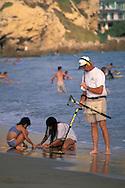 Man using metal detector on sand peach next to kids, Corona del Mar, Newport Beach, California