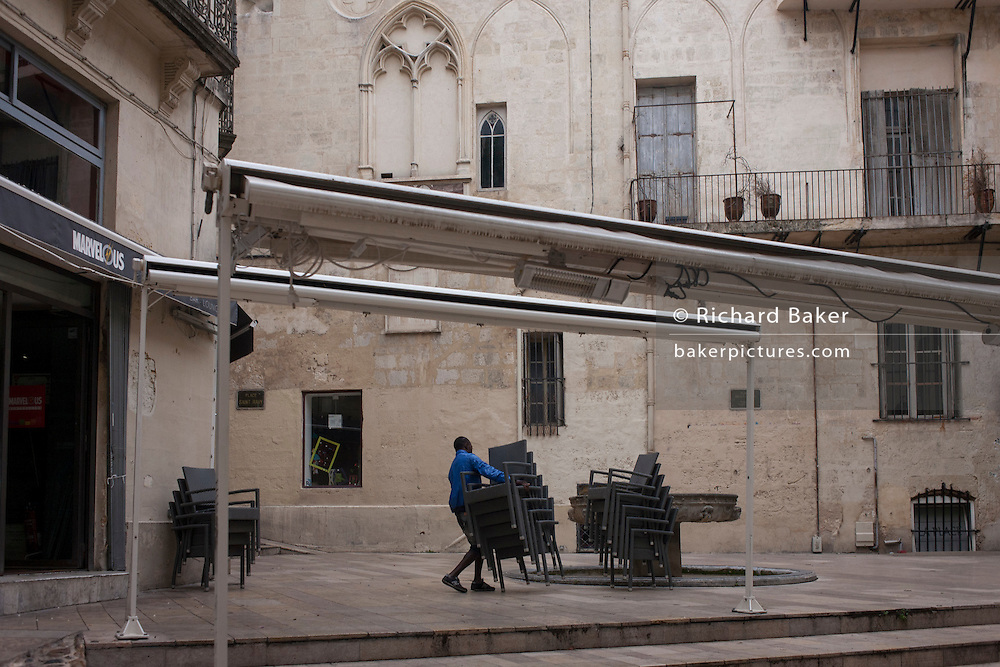 A cafe worker struggles with stacked chairs in an old square of Montpellier, south of France.