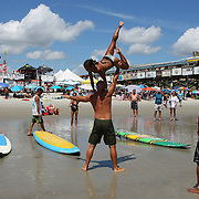 A tandem surf couple practices their moves on the beach during the 28th annual National Kidney Foundation, Rich Salick Pro/Am surf festival takes place at the the Cocoa Beach pier on Saturday,  September 2, 2013 in Cocoa Beach, Florida. This event raises thousands of dollars for people with kidney disease and also benefits the services of the NKF of Florida. (AP Photo/Alex Menendez)