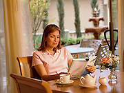 A woman reads a book at a dining table while staying at a luxurious Country Club & Resort