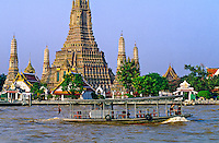 Ferry boat on the Chao Phraya RIver and Wat Arun (Temple of Dawn) in background, Bangkok, Thailand