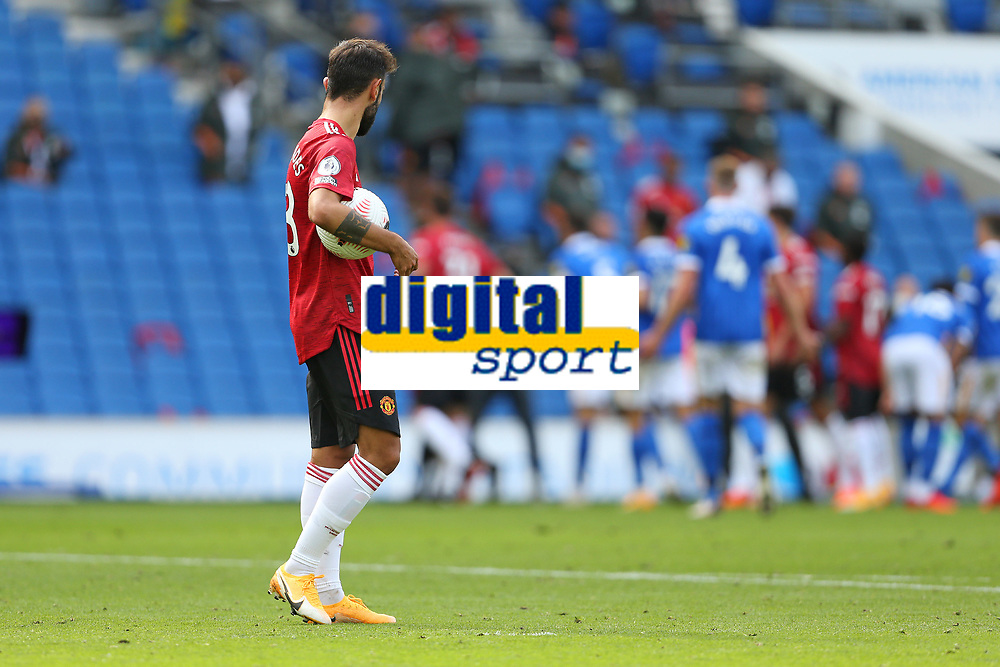 Football - 2020 / 2021 Premier League - Brighton and Hove Albion vs. Manchester United<br /> <br /> Bruno Fernandes of Manchester United quietly waits with the ball by the penalty spot as both teams crowd round Referee Mr Chris Kavanagh and the VAR screen during the Premier League match at The Amex Stadium Brighton <br /> <br /> COLORSPORT/SHAUN BOGGUST