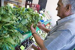 Older man out shopping for vegetables,