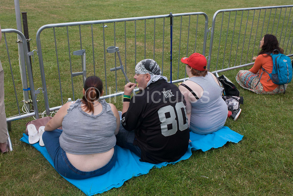 Three large family members eat a picnic in a south London park. Sitting to watch an event in the main arena of the Lambeth Couty Show, the large people continue to eat while seated on a blanket on the park grass. Obesity rates in the UK are the highest in Europe and have increased dramatically over the past few years to such an extent that in excess of 20% of the population are now obese and the costs to the UK economy exceed £3 billion per year. The high prevalence of obesity in adults within England is alarming, with national averages of over 40% of males overweight and more than 20% obese in the 16-75 year age range, while in women the averages are lower for the overweight classification but higher for obesity.