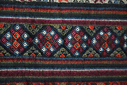 Close up of a woollen yathra blanket from the Bumthang region in central Bhutan. Yathra is a hand woven fabric made from the wool of sheep and yak and is the most famous textile product of Bumthang. Produced on a Tibetan style loom, yathra cloth is woven in strips and made into skarfs, jackets, blankets; table cloths and bags.