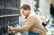 A member of the public puts a Christian cross on the gates on Buckingham Palace In memory of Prince Philip The Royal Highness the Duke of Edinburgh, London on 9 April 2021.