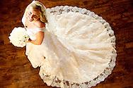 Bridal picture taken in white wedding dress from above against beautiful dark hardwood floors.