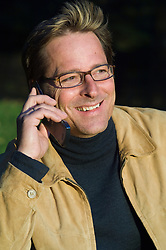 Man wearing glasses and a tan jacket smiling while talking on his mobile phone