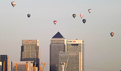 © Licensed to London News Pictures. 07/06/2015. London, UK. Hot air balloons rise over the London skyline on a summer morning. 50 Balloons took to the skies as part of the Lord Mayor's Regatta to raise money for charity. the last mass ascent balloon flight over London was over 20 years ago.Photo credit : Andrew Christy/LNP