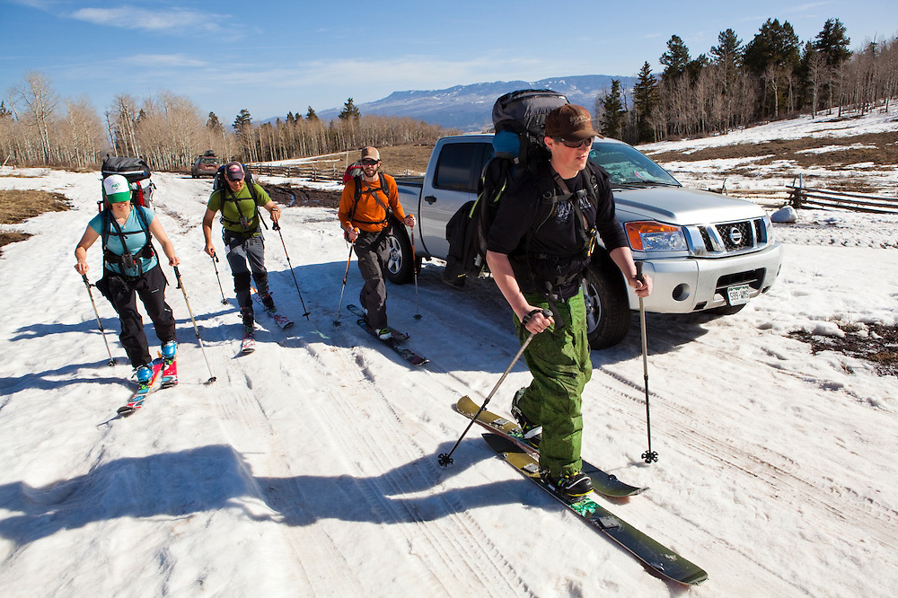 Backcountry skiers skin up a road into the San Juan Mountains, Colorado.