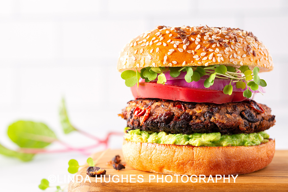 Healthy grilled black bean burger on a sesame seed bun with avocado, tomato, red onion, and microgreens,