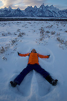 Russell Laman (age 12) makes a snow angel below the Tetons.<br />Grand Teton National Park, Wyoming