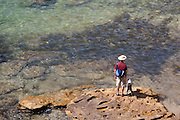 Man and his dog looking out to sea. Gordons bay, Sydney, Australia