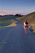 Cyclist biking on bicycle along twisting mountain road, Bolinas Ridge, Mount Tamalpais State Park, Marin, California