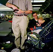 Pre-9/11, an American family of mother, father and young child prepare for their flight from Los Angeles (LAX) airport. As the husband and daddy, the man checks his wallet for cash while the mom adjusts the struggling baby boy's clothing before strapping the child into his buggy and their flight to another US city. Los Angeles International Airport is the primary airport serving the Greater Los Angeles Area, the second-most populated metropolitan area in the United States.