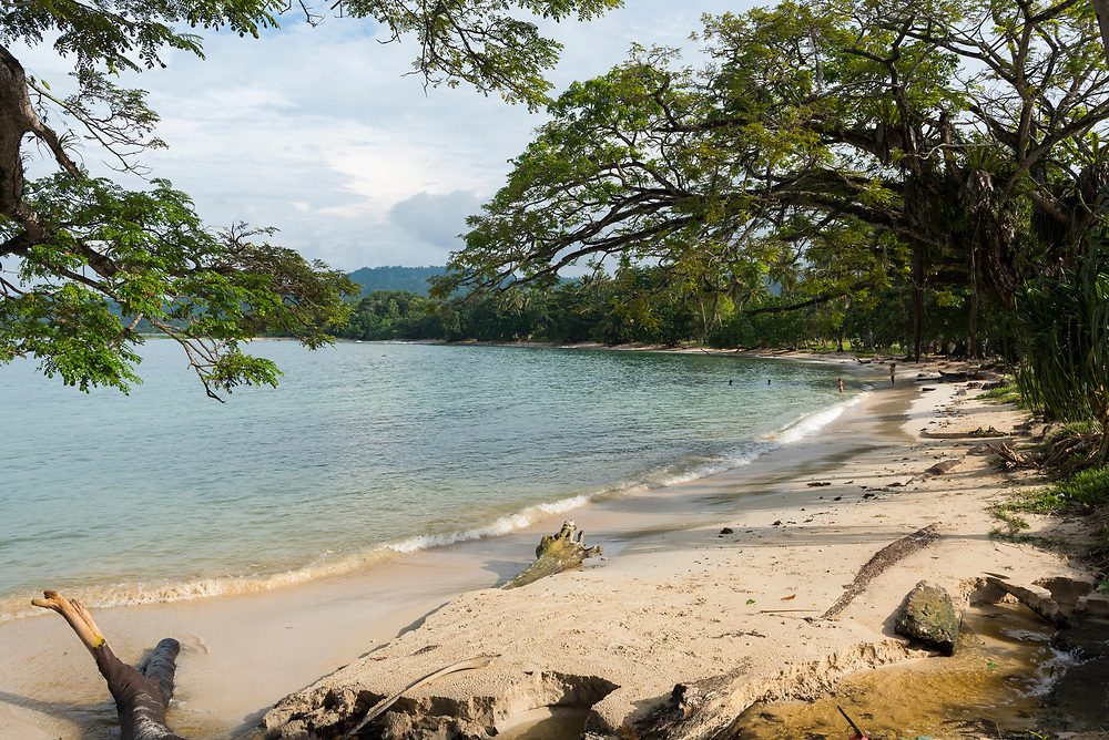 Beach in Vanimo, Papua New Guinea, with a woman watching three children playing in the sea (2017)
