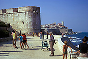People on the waterfront outside the walled fortress ramparts at Antibes, French Riviera, France 1974