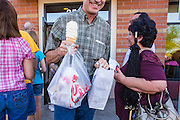 01 AUGUST 2012 - CHANDLER, AZ: A man squeezes through the crowd after buying take out chicken at a Chick-fil-A Wednesday. Thousands of people stood in line for up to an hour at the Chick-fil-A in Chandler, AZ, a suburb of Phoenix Wednesday after MIKE HUCKABEE, the former governor of Arkansas and Fox News host, called for a national ''Chick-fil-A Appreciation Day,'' a day on which he encouraged people to patronize the fast food chain, this after DAN CATHY, President and CEO of Chick-fil-A, who is a fundamentalist Christian, made public his views against same sex marriage, causing an outcry from political leaders and Gay rights advocates.     PHOTO BY JACK KURTZ