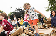 21/07/2018 repro free:  Art Ó Fártharta from knocknacarra demolishing cardboard one of the large scale structures that appeared in a matter of hours built solely from cardboard. <br /> <br /> The People Build at Galway International Arts Festival Under the guidance of French artist, Olivier Grossetete and his team, The People Build saw over 600 volunteers and members of the general public transform cardboard boxes into a church steeple and a bridge. This spectacular architectural event won the hearts of festival audiences and encouraged a sense of community where everyone could get involved. The structure built at Eyre Square was inspired by St. Nicholas' Church in Galway and the bridge at Waterside was positioned at the location of Galway's River Corrib Viaduct, once part of the famous Galway to Clifden Railway.<br /> <br /> It is estimated that almost 4 tonnes of cardboard were used across the two builds. Following the constructions, children and grown-ups alike joined forces in a massive celebratory demolition, which saw the cardboard structures come tumbling down amidst shrieks of joy and delight.<br /> <br /> Walsh Waste & Recycling have once again joined forces with Galway International Arts Festival to ensure there was no unnecessary waste following the event and were on hand to take away the crushed cardboard to be recycled. Photo:Andrew Downes, xposure