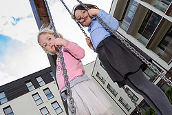 Friends Zara, 3, left and Sylvie, 6 play on the swing. Social housing residents are up in arms after having their children forbidden from using a play area overlooked by their homes as it is said to be only available to the children of those who have bought properties at the new Baylis Old School housing development in Lambeth, South London . London, March 26 2019.