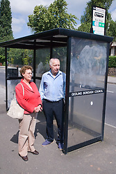 Older couple waiting at a bus stop,