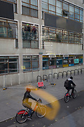 Cyclists pedal along a cycle lane beneath workmen high up on a building exterior, on 14th September 2017, in London, England.