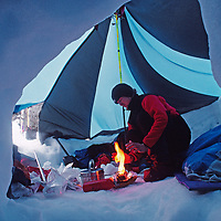 A mountaineer cooks in a remote Patagonian snow cave.