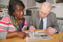 Carer and pensioner doing crossword in newspaper.