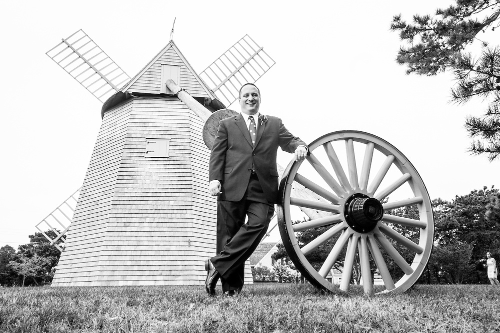 A groom poses at the Chatham windmill with his bride walking into frame in the distance.