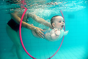 6 month old baby swimming through a loop, underwater in a swimming pool as seen from below water surface