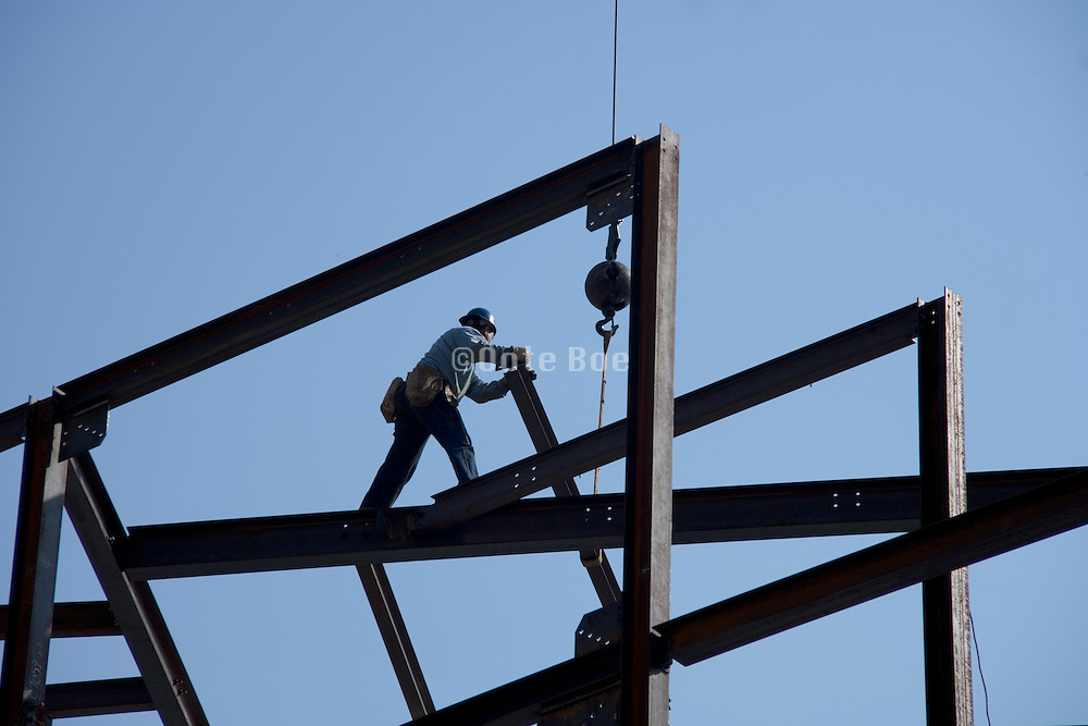 ironworker standing on top of a steel framework meanwhile positioning a girder into place