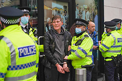 © Licensed to London News Pictures. 21/11/2020. Liverpool, UK. Police officers arrested a protester during an anti-lockdown protest in Liverpool. Thousands of anti-lockdown protesters took to the streets across the country against lockdown . Photo credit: Ioannis Alexopoulos/LNP