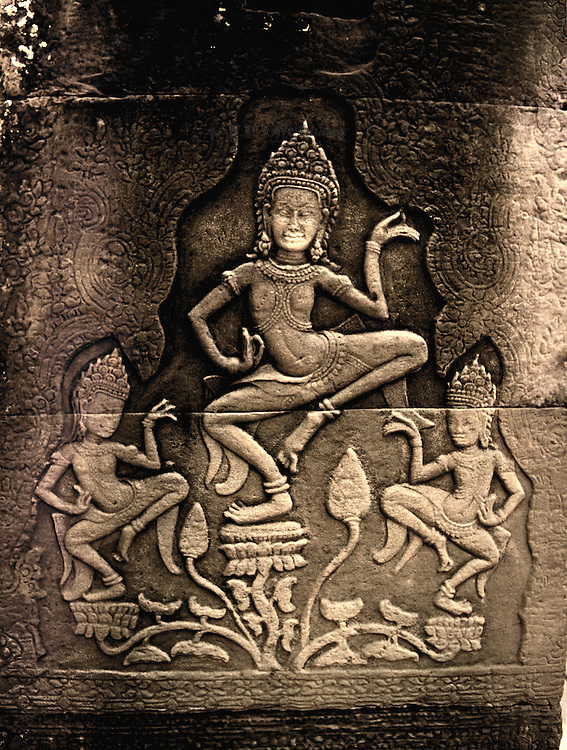 Shallow relief of a trio of apsara dancers on a wall of one of the Angkor temples.  The center figure is larger and above the two other figures.  knees jutting out to the side.